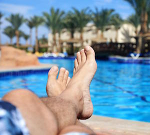 mans-feet-near-swimming-pool